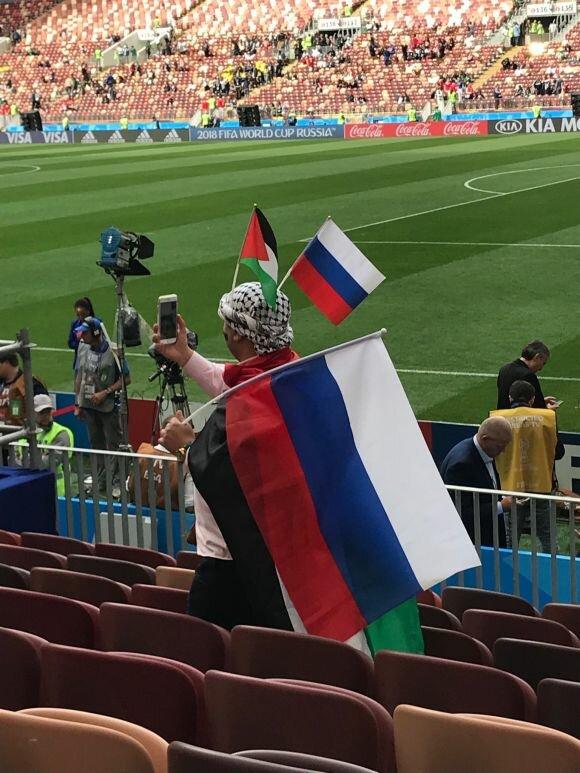 #صورة | مشجع فلسطيني يساند #روسيا في مباراة الإفتتاح أمام #السعودية و يحمل فوق رأسه الكوفية العربية و علم #فلسطين و بجانبه علم روسيا 